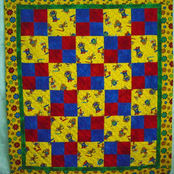 Yellow baby quilt with robots.