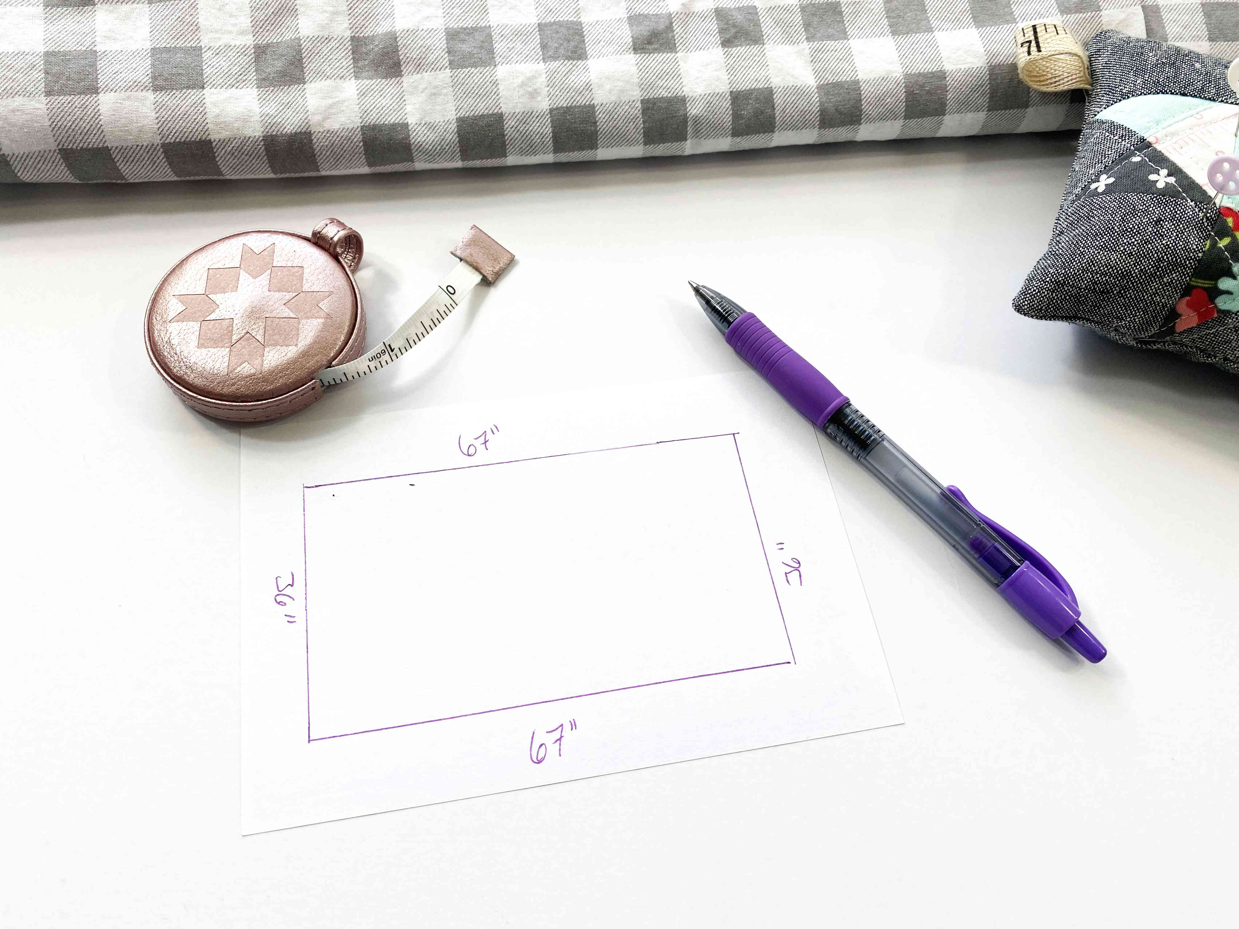 A diagram of a table with a pen and other sewing notions