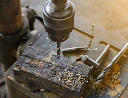A drill press with a piece of wood