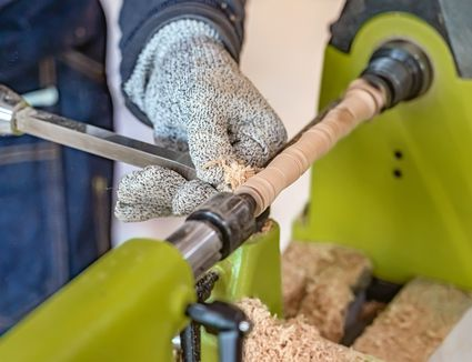 Carpenter man is carving the wooden stick.