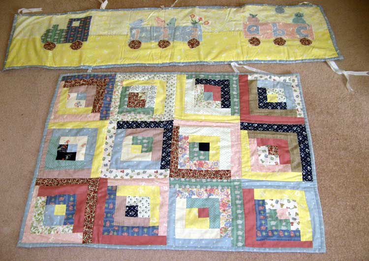 Baby quilt and yellow train bumper.