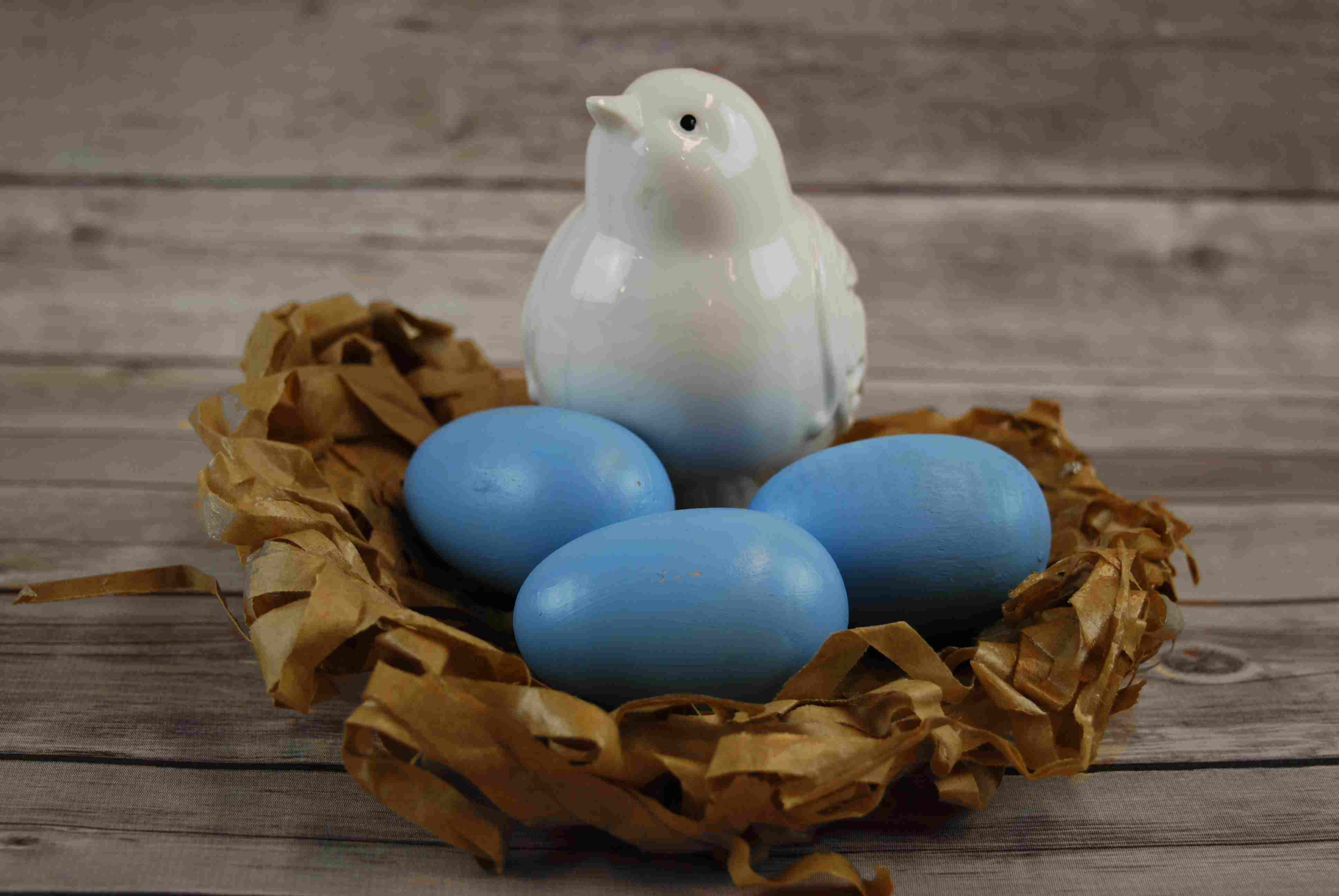 ceramic bird and wooden eggs in a paper nest