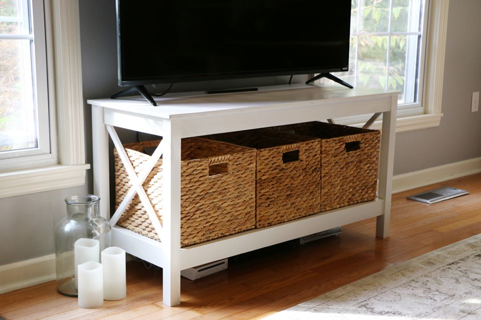 A white DIY tv stand with baskets on lower shelf