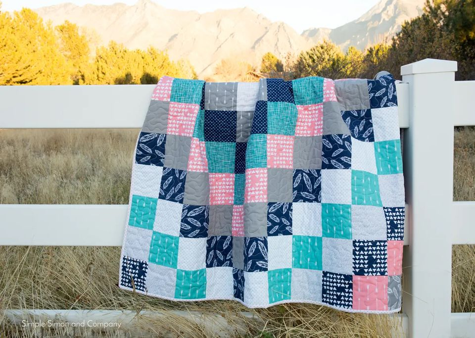 A colorful quilt hung over a white fence