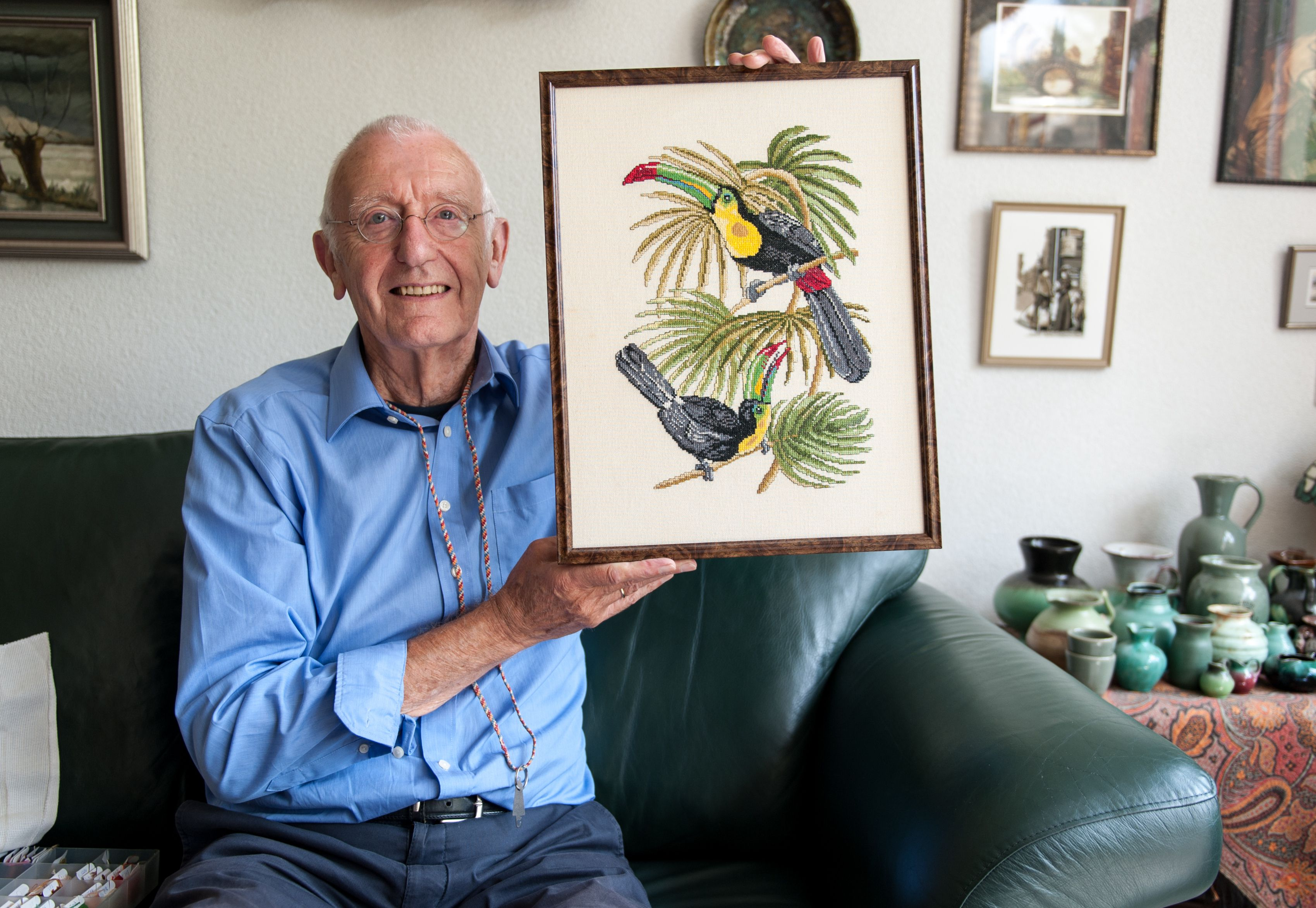 Senior man proudly showing his embroidered artwork