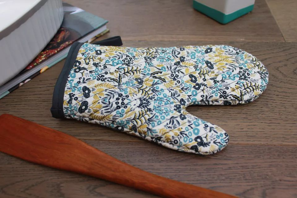 A floral oven mitt laying on a table