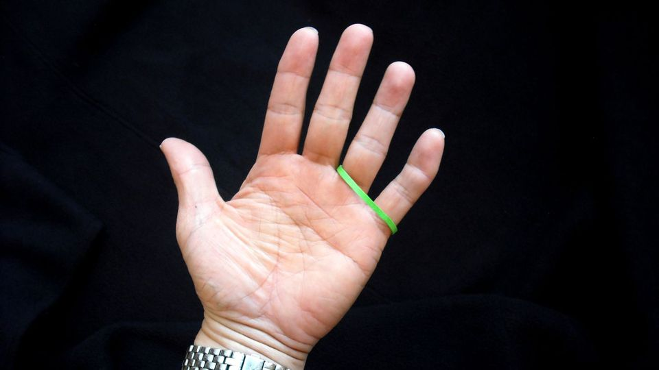 A trick with rubber band wrapped around ring and pinky fingers