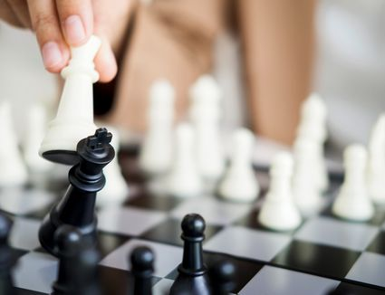 Close-Up Of Human Hand Playing Chess