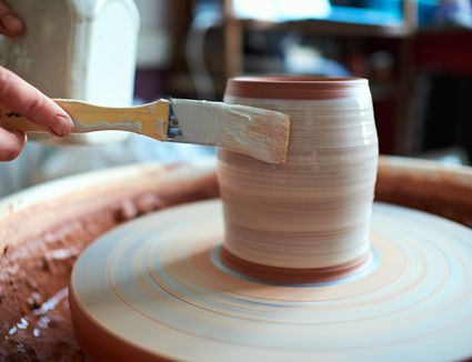production process of pottery. Application of glaze brush on ceramic ware.