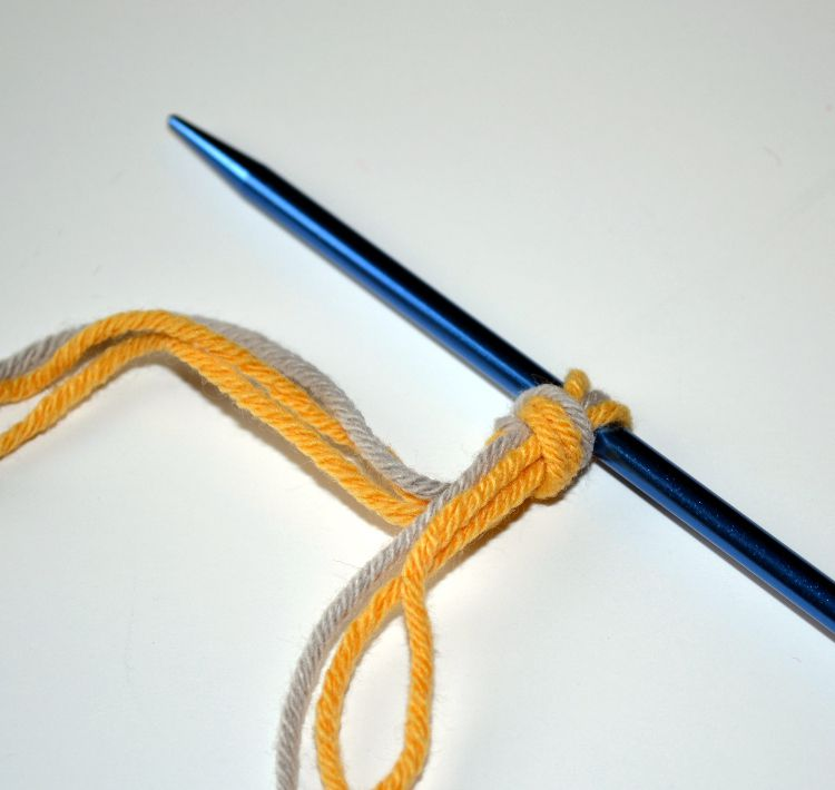 A slip knot formed with three strands of yarn to prepare for the two-color cast on.