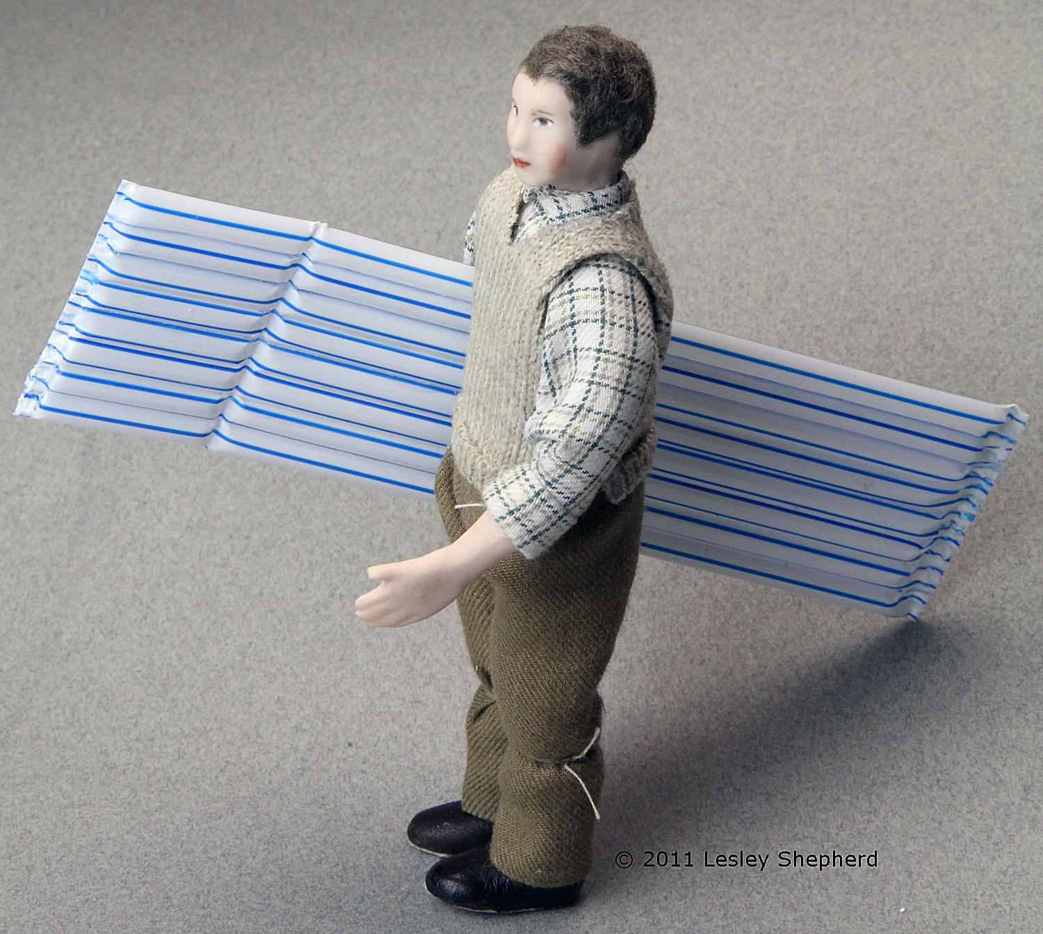 Dollhouse doll with a 1:12 scale miniature air mattress made from plastic drinking straws.