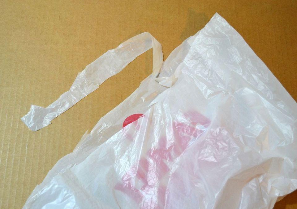 Strip coming off the top of a plastic bag.