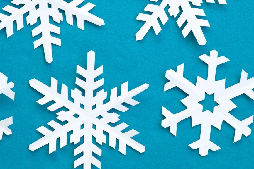 Cut Out Paper Snowflakes On A Blue Background