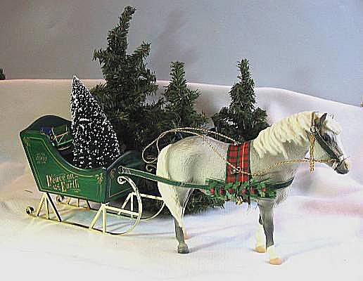 Breyer model horse with sleigh and Christmas trees.