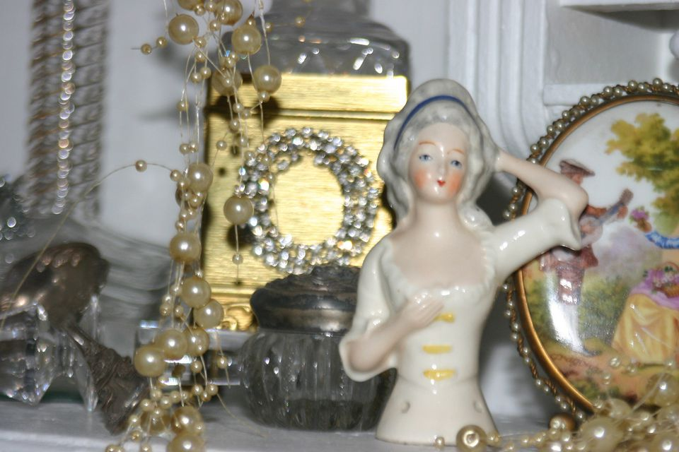 Vintage pincushion half doll on a shelf with costume jewelry.