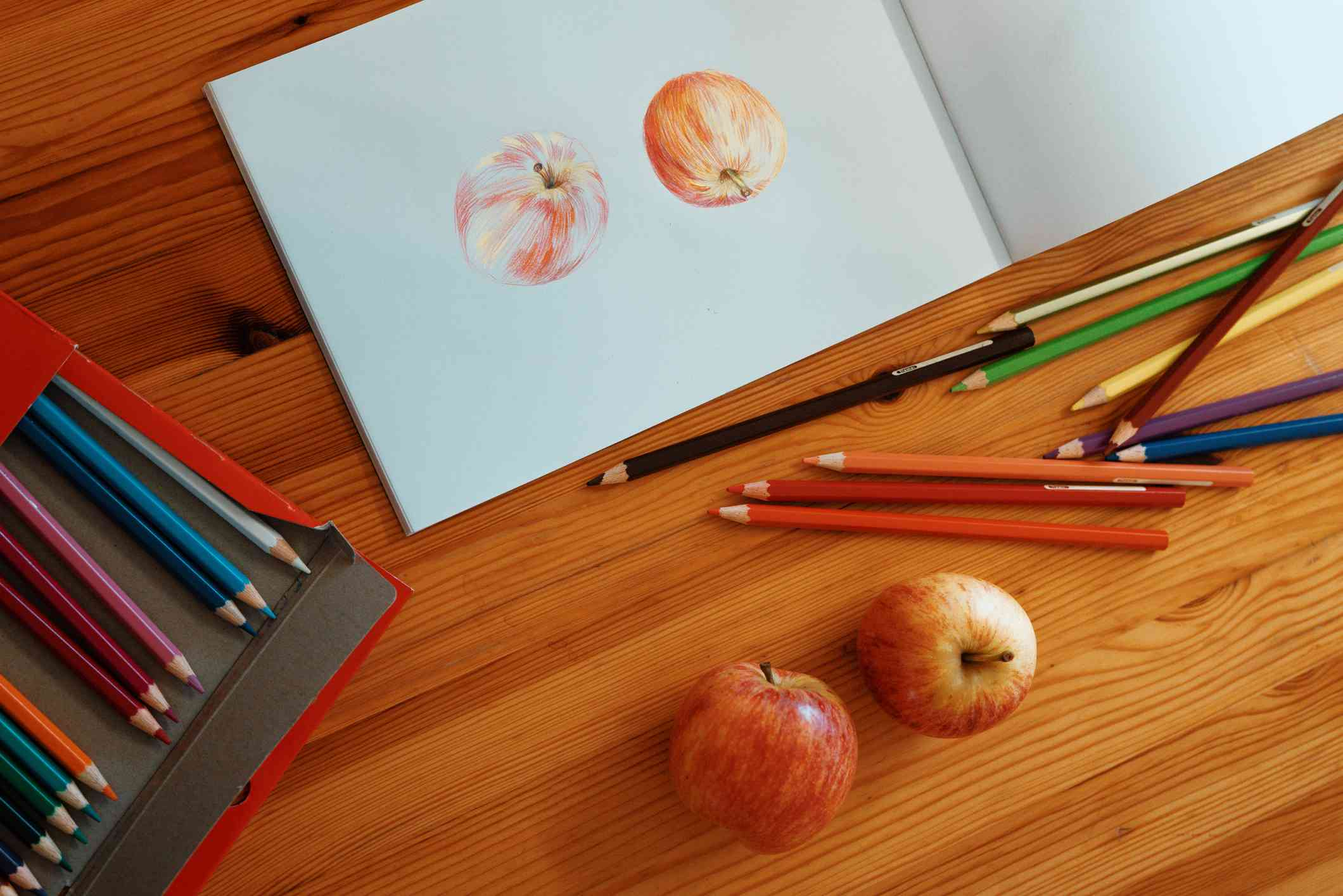 Draw Two Apples Using Colour Pencils on the Table