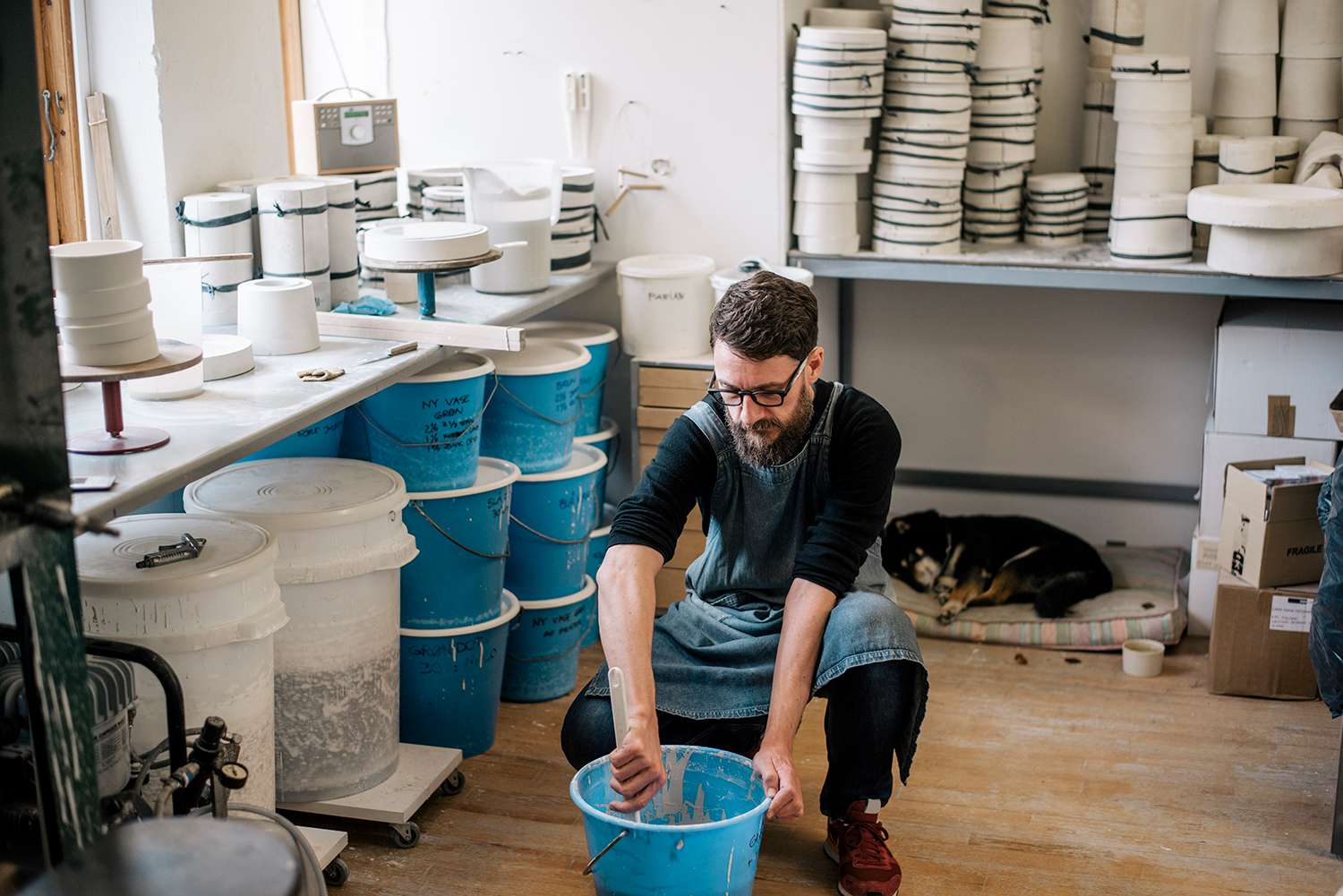 Potter in workshop with his dog