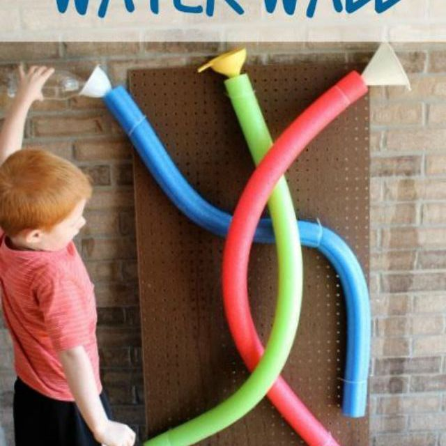 Boy using pool noodle water wall with red, green, and blue noodles, funnels, and cup.