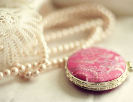 Lace, a pocket mirror and pearl necklace