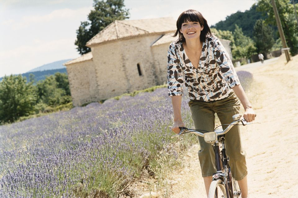 Woman riding bike by lavender field