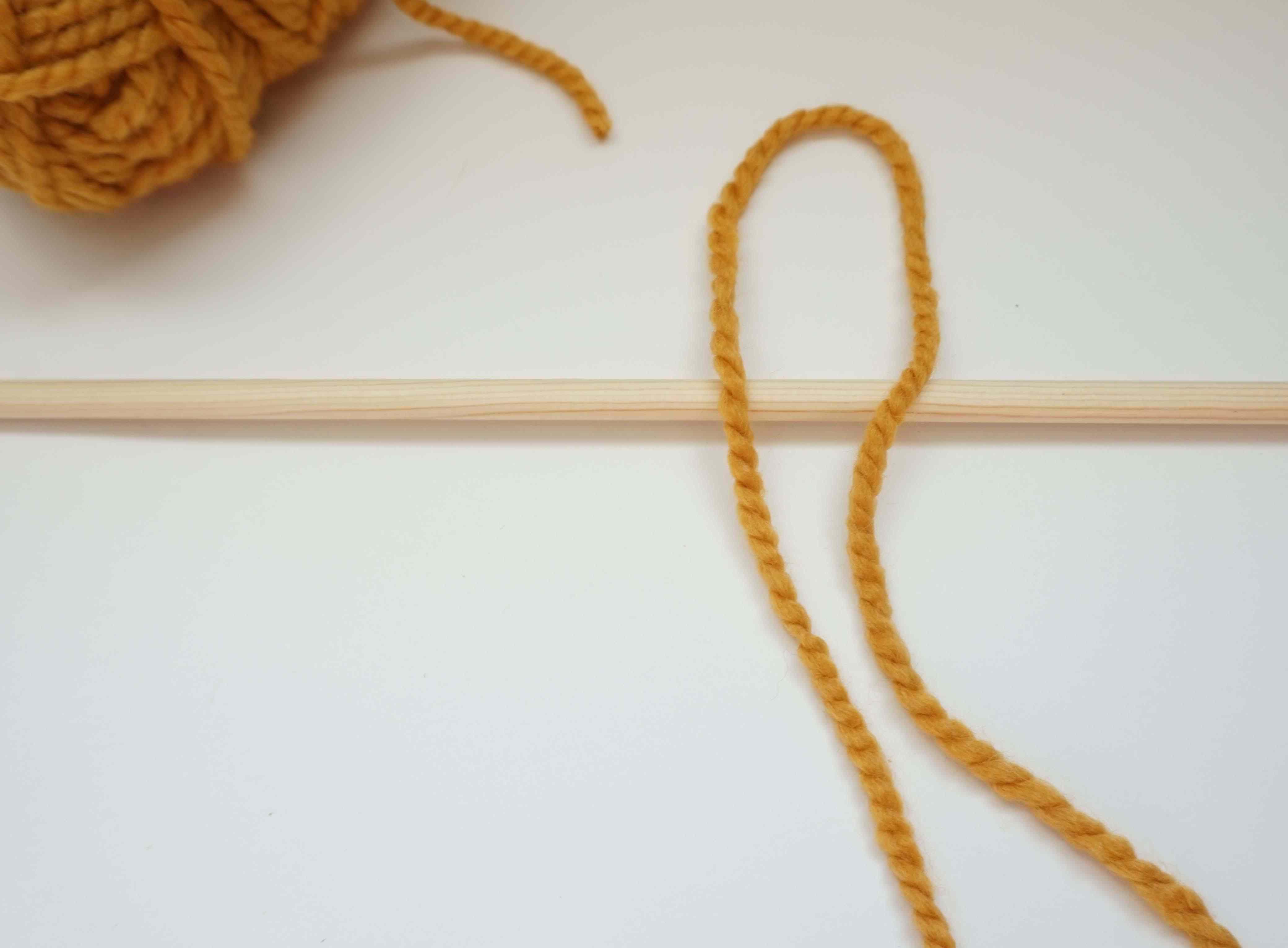 Yarn looped over dowel.
