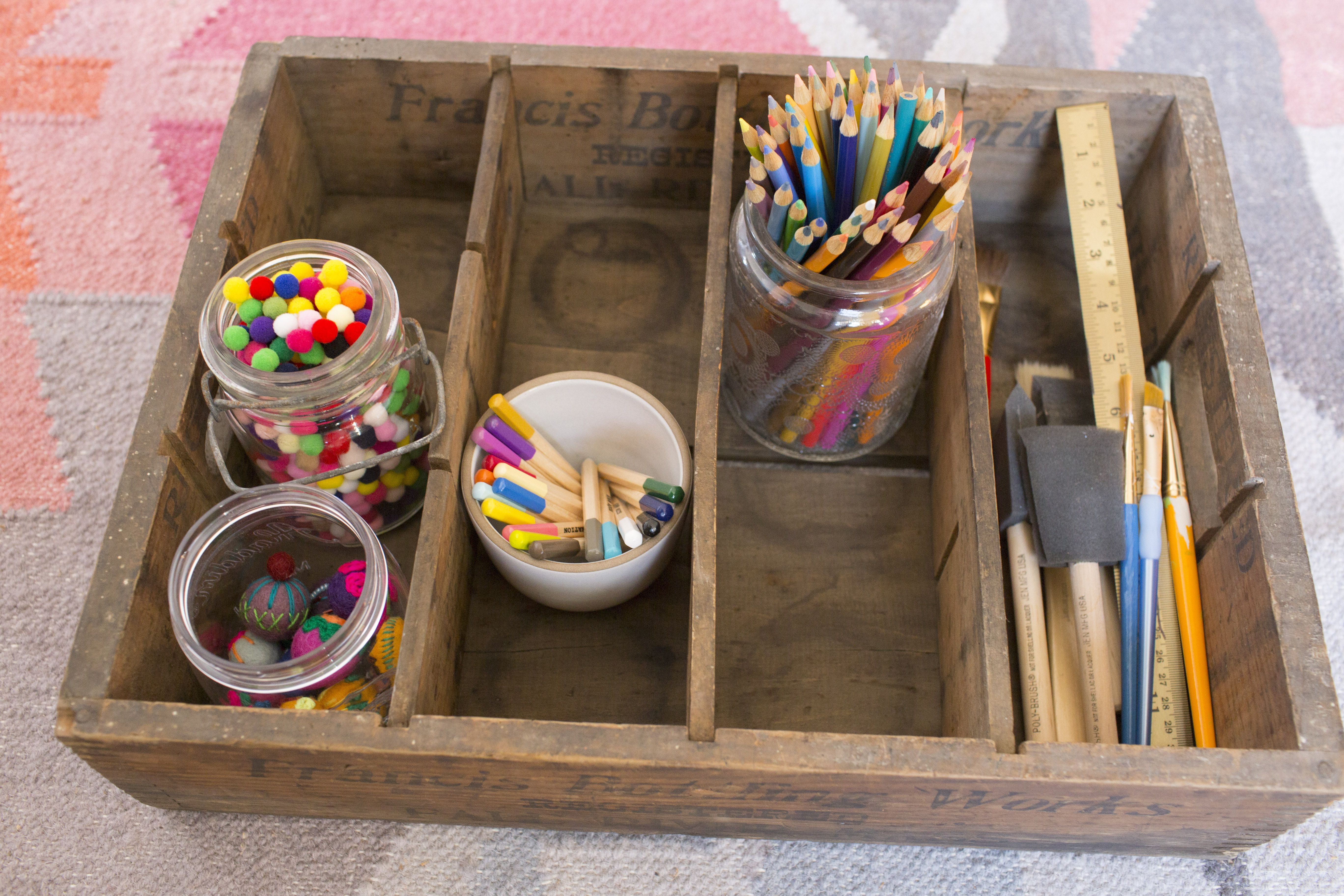 art supplies in a wooden crate