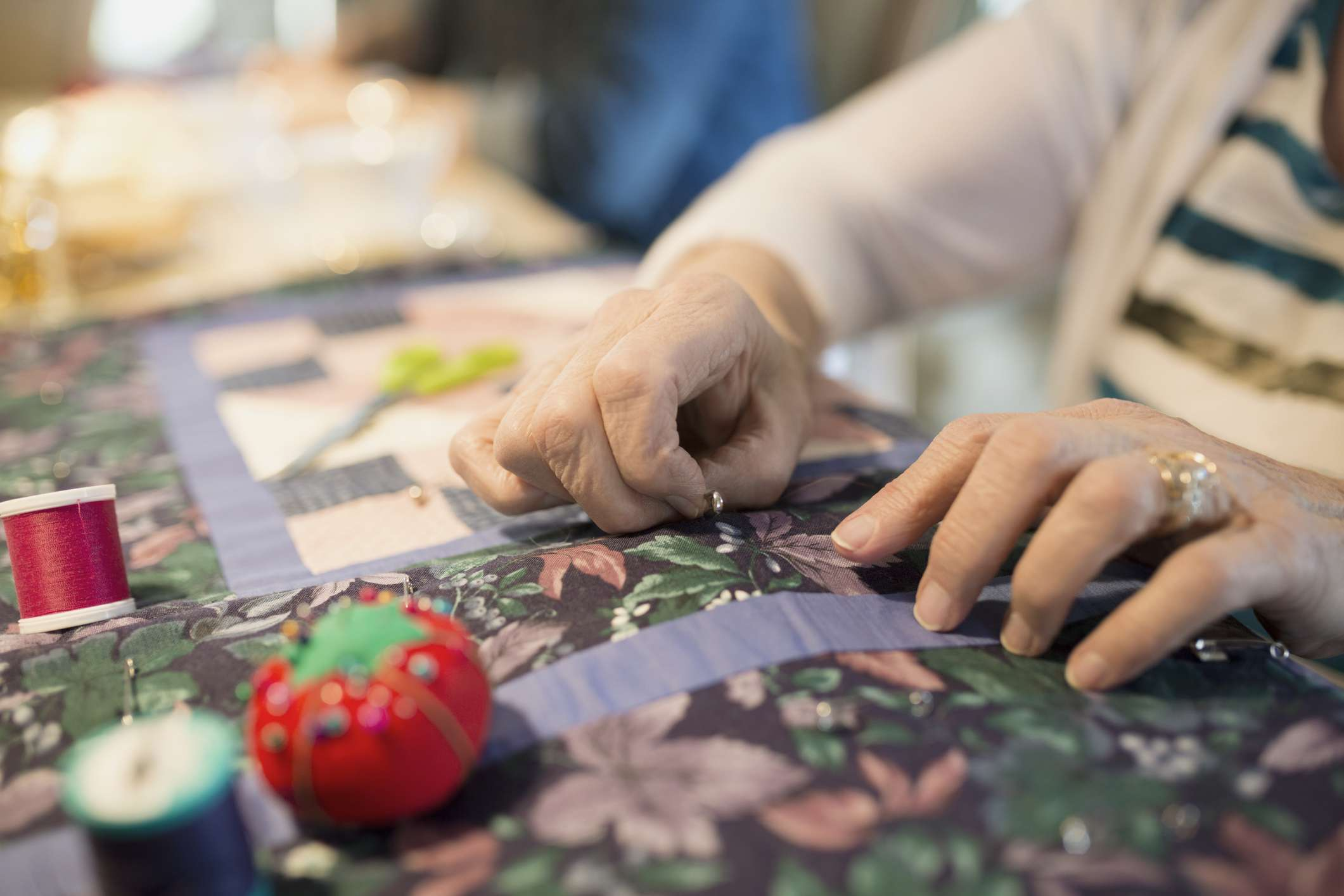 senior woman sewing quilt