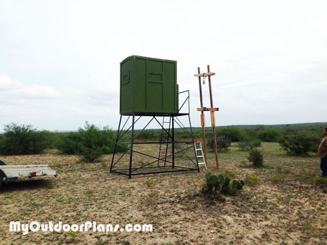 A green deer stand in a field built from a free deer stand plan