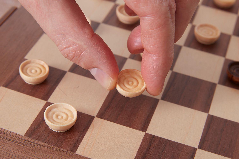 person moving a white checker