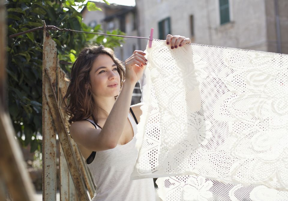 Woman hanging tablecloth on clothesline