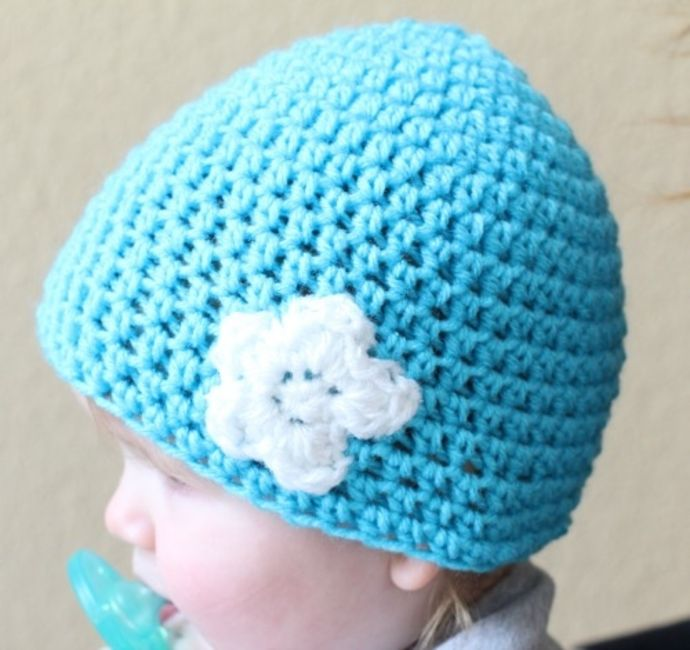 Blue HDC crochet beanie with white flower on a toddler's head.