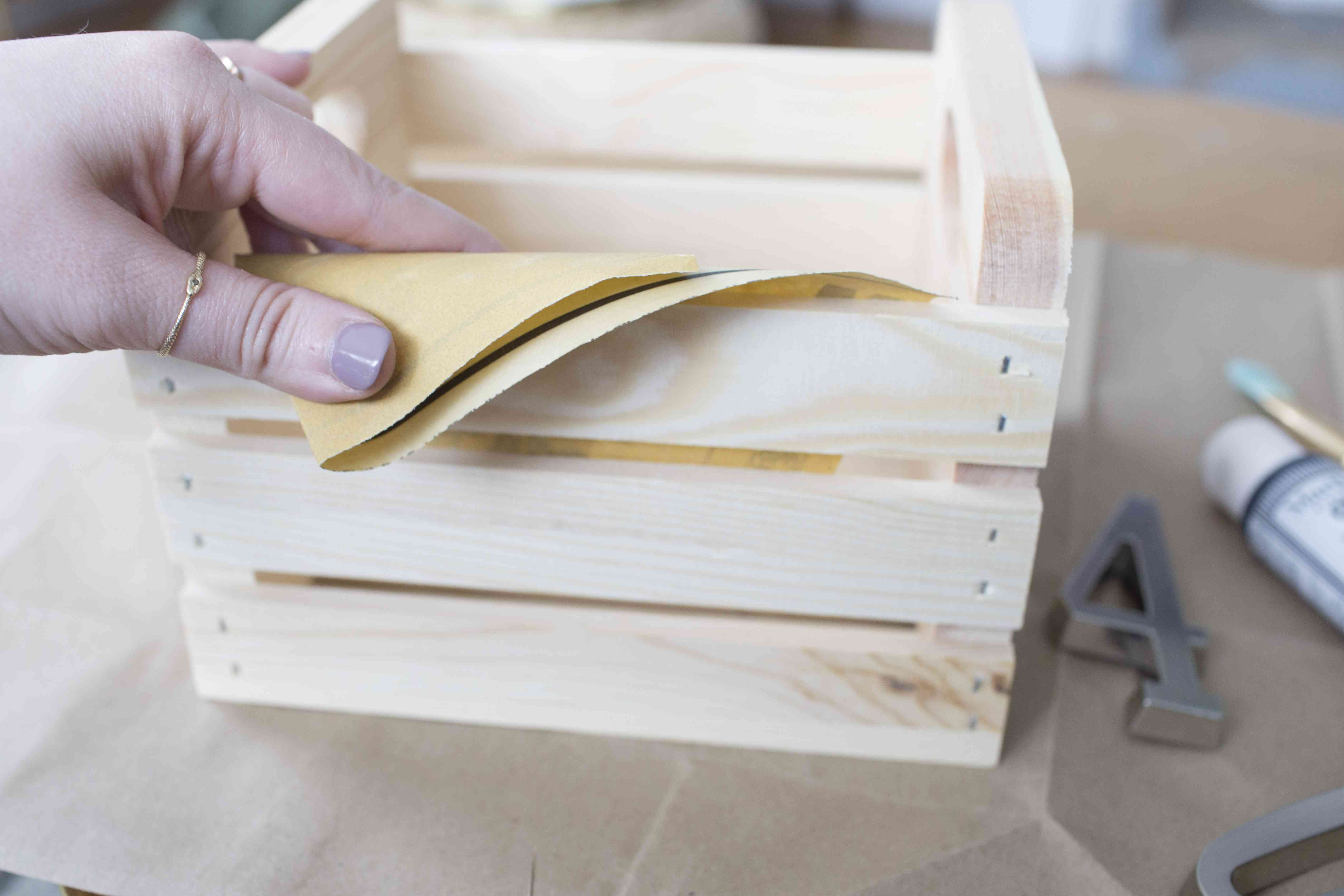 A hand sanding down a small wooden crate