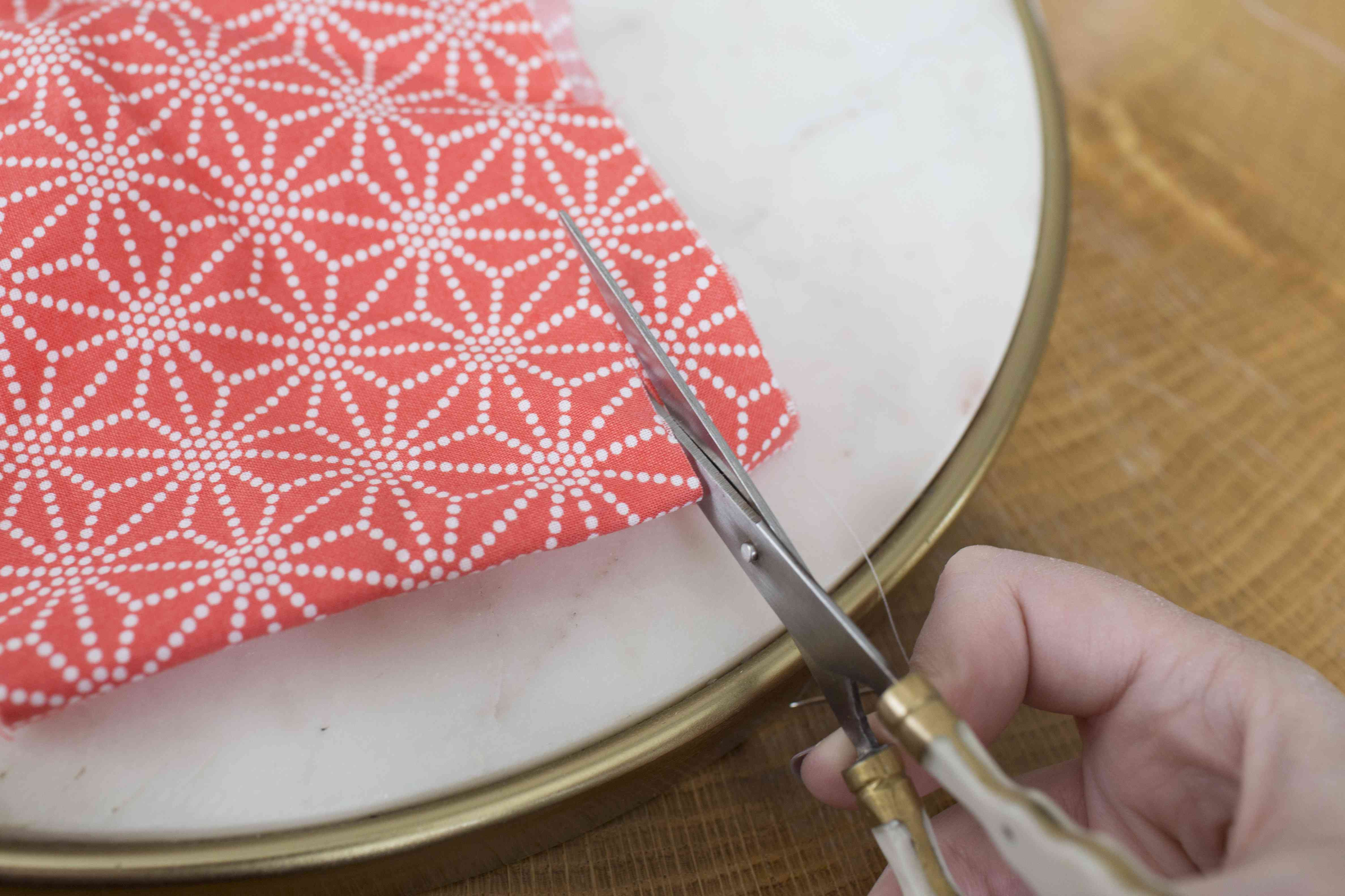 Scissors cutting into brightly patterned coral colored fabric