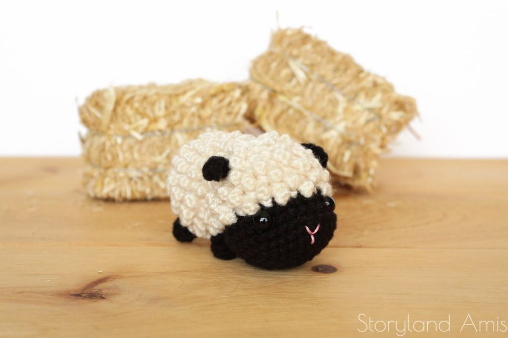Crochet lamb with black face in front of mini bales of hay.