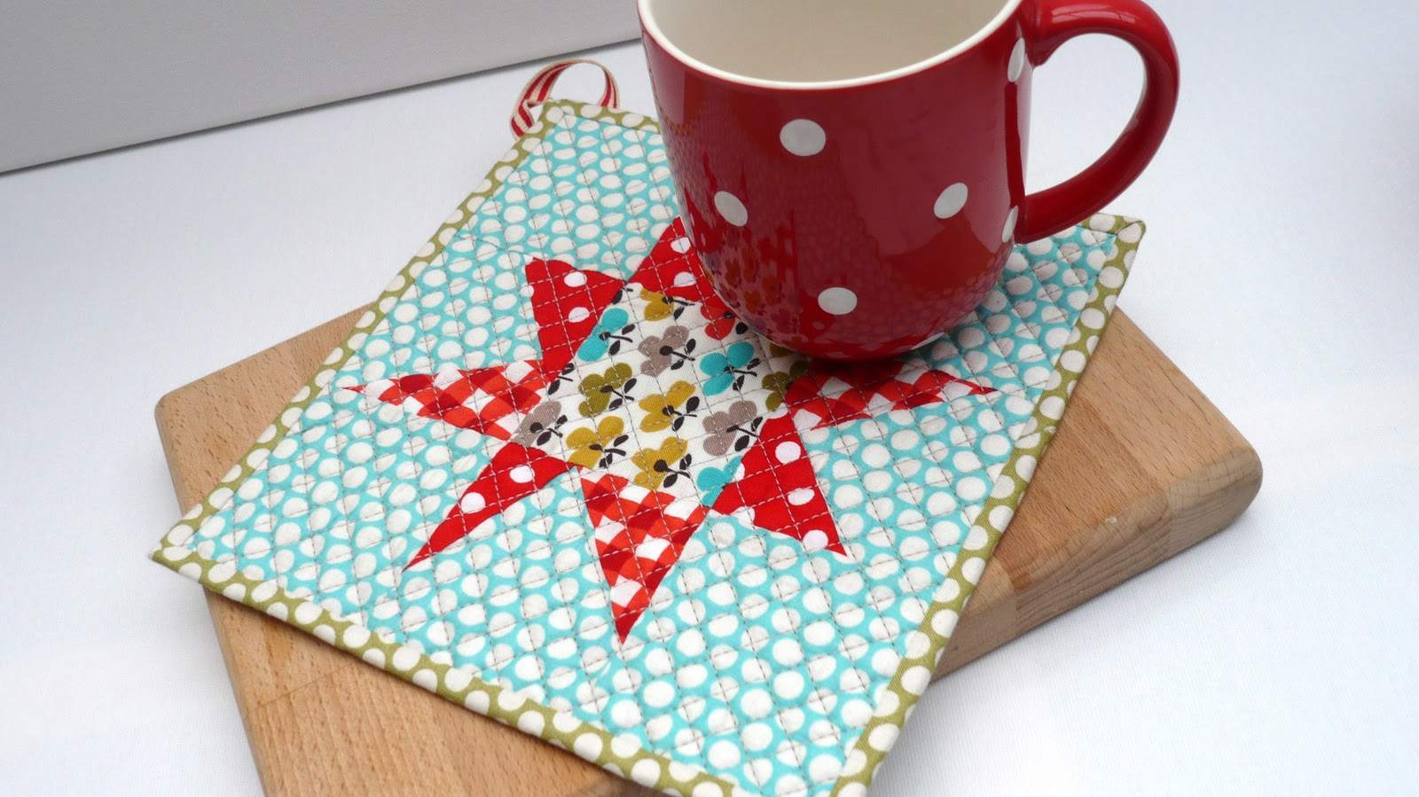 A patchwork star pot holder with a red coffee mug