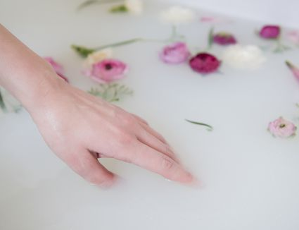 Woman's hand trying out a milk bath.