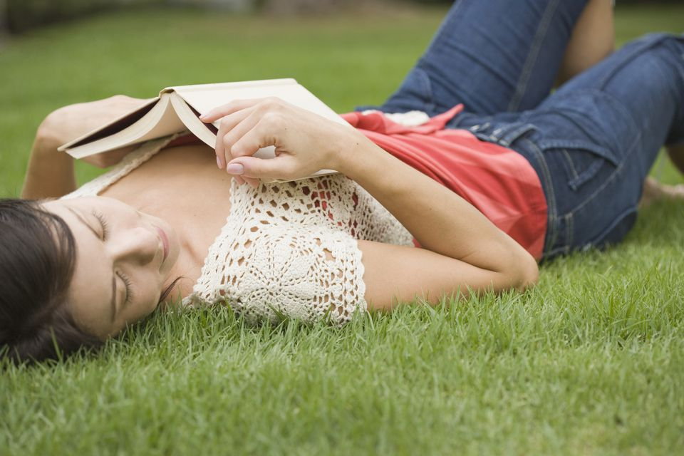Woman laying on a grassy lawn with a book