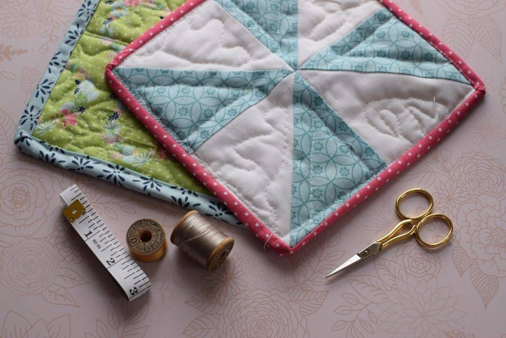 Two quilted pot holders with scissors, thread, and measuring tape on a table
