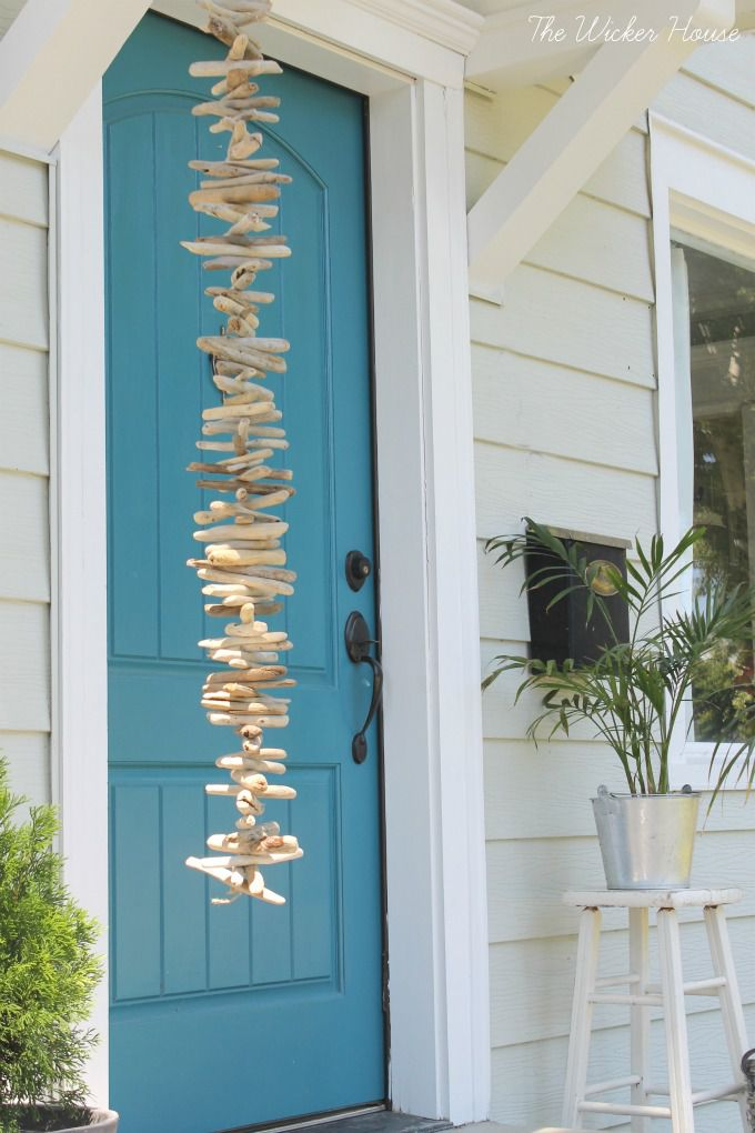 Driftwood design hanging from the front entryway in front of a blue door.