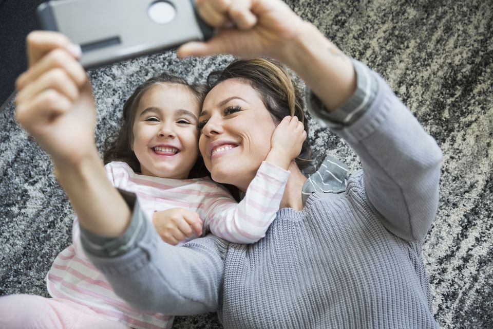 Overhead view enthusiastic mother and daughter taking selfie laying on rug