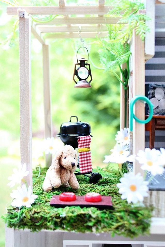 A close-up of a dollhouse porch with dog and grill
