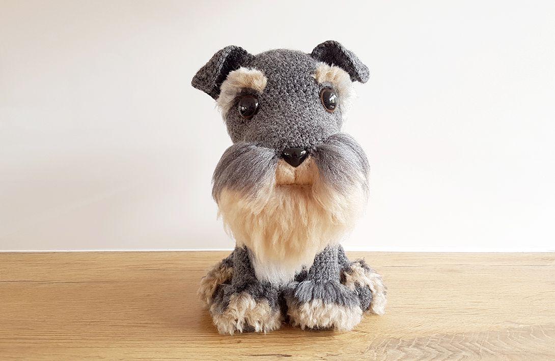 A crochet schnauzer dog with furry eyebrows and beard.