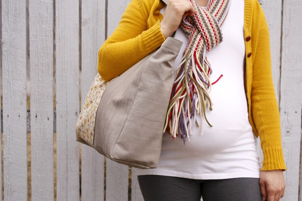 A woman in a yellow sweater holding a tote bag
