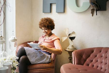 Woman sitting in designer furniture shop and using tablet pc - How To Value Your Antiques And Collectibles