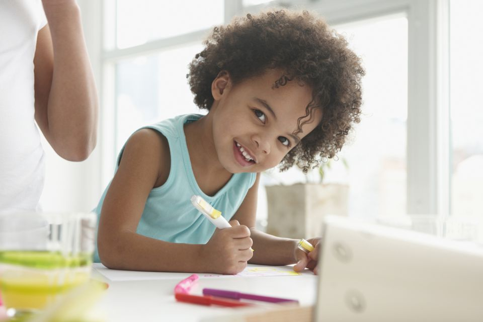 A girl sitting at a table coloring.