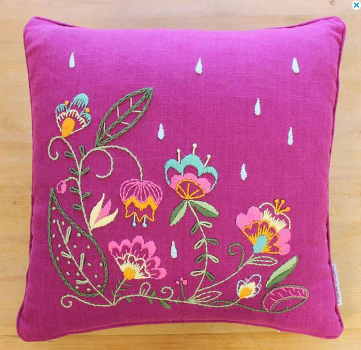 Bright pink pillow with flower embroidery.