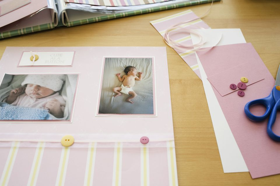 Baby scrapbook being made next to buttons, ribbon, and scissors