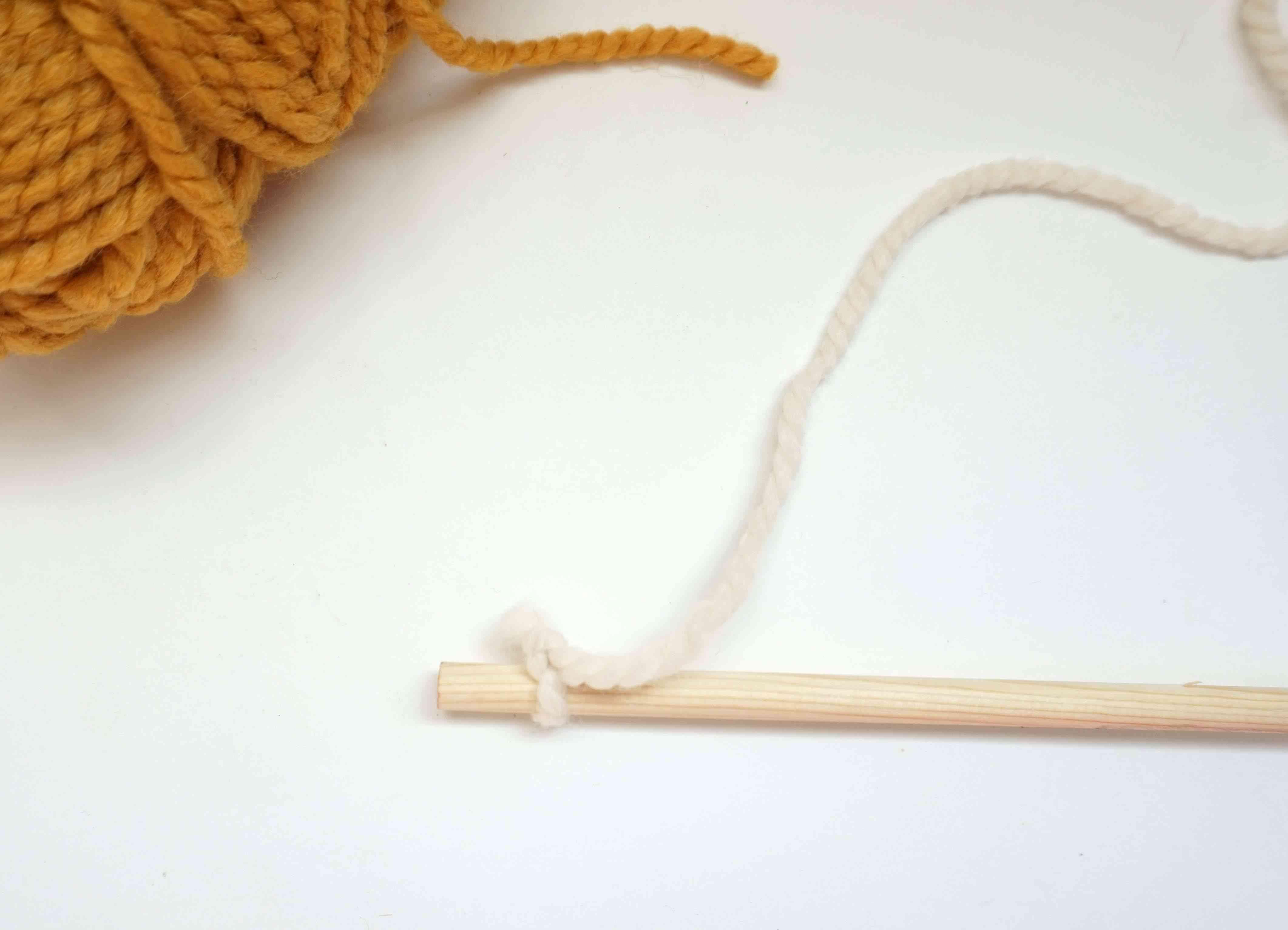 Yarn tied to dowel.