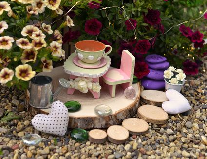 Tiny table, chair and cup by flowerpot with petunia flowers in the garden.