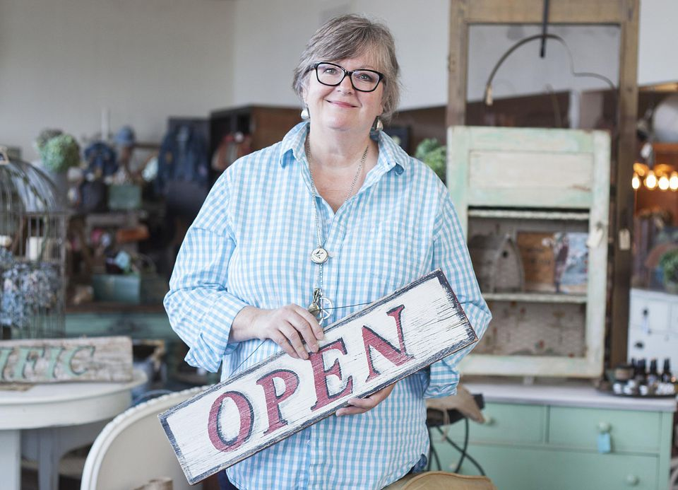 Woman with open sign and antiques